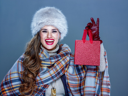 Winter things. Portrait of smiling elegant woman in fur hat isolated on cold blue background showing small red shopping bag