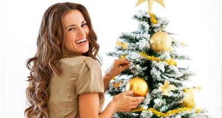クリスマス ツリーを飾る笑顔の若い女性の肖像画