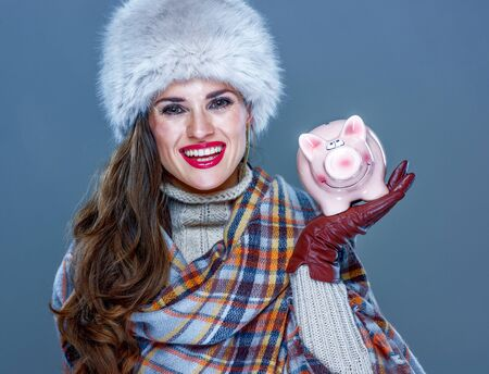 Winter things. happy young woman in fur hat isolated on cold blue background showing piggy bank Stock Photo