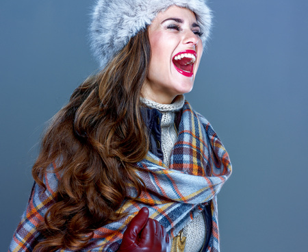 Winter things. Portrait of happy elegant woman in fur hat isolated on cold blue rejoicing Stock Photo