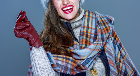Winter things. Closeup on smiling trendy woman in fur hat isolated on cold blue snapping fingers