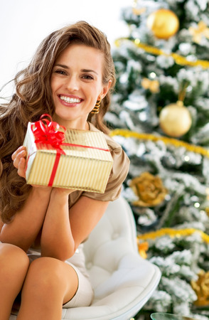 Smiling young woman with christmas present box near christmas tree 스톡 콘텐츠 - 99981824