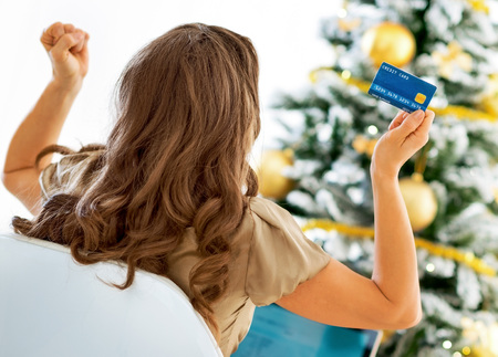 Young woman with credit card and laptop rejoicing success near christmas tree Stock Photo