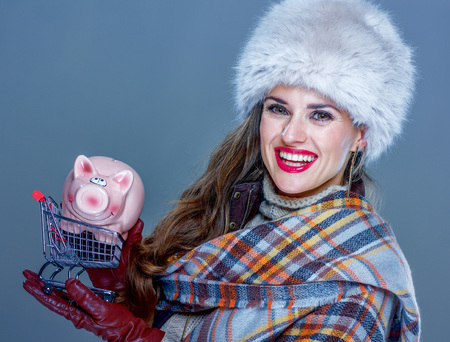 Winter things. Portrait of happy young woman in fur hat isolated on cold blue holding shopping trolley with piggy bank