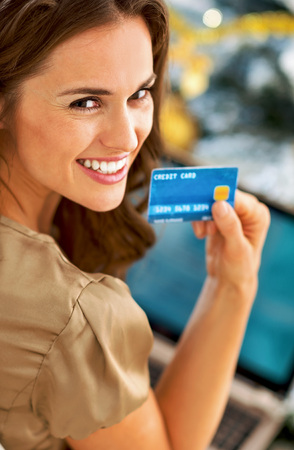 Portrait of smiling young woman with credit card using laptop in front of christmas tree