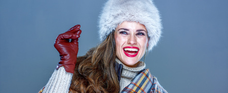 Winter things. Portrait of happy trendy woman in fur hat isolated on cold blue background snapping fingers and looking on copy space Stock Photo