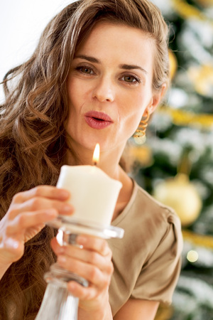 Young woman blowing candle in front of christmas tree 版權商用圖片
