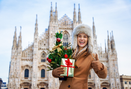 Portrait of happy modern woman in Milan, Italy with Christmas tree and gift showing thumbs up 스톡 콘텐츠 - 99982159