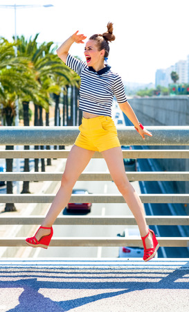 Nosing around, having fun. Full length portrait of smiling stylish woman in yellow shorts and stripy shirt outdoors in the city looking into the distance and jumping
