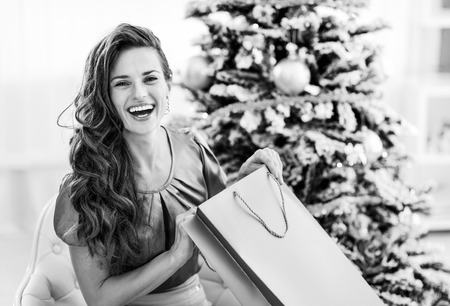 Happy young woman opening shopping bag near christmas tree
