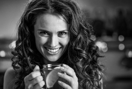 Portrait of happy young woman with cup of ginger tea Foto de archivo - 99982709