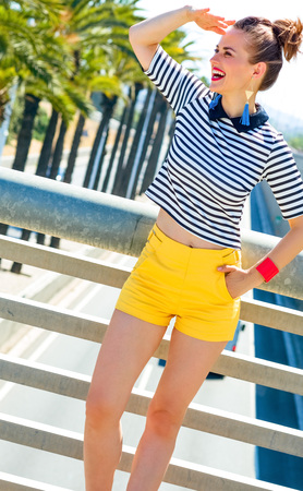 Full length portrait of happy elegant fashion-monger in yellow shorts and stripy shirt in Barcelona, Spain looking into the distance