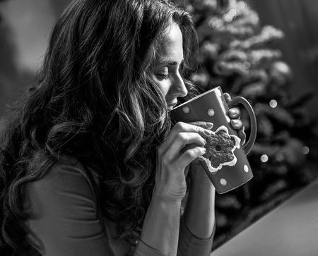 Feliz, mulher jovem, tendo, um, xícara chocolate quente, com, marshmallows, e, biscoito, frente, árvore natal Foto de archivo - 91804199
