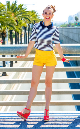 Full length portrait of smiling trendy fashion-monger in yellow shorts and stripy shirt in Barcelona, Spain having fun time Stock Photo