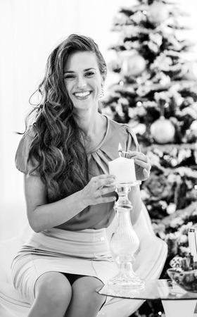 행복 한 젊은 여자 조명 촛불 크리스마스 트리 근처