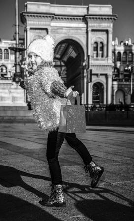 ミラノ、イタリアで赤いショッピングバッグを持つ幸せなエレガントな女の子の完全な長さの肖像画