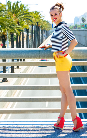 Full length portrait of happy stylish fashion-monger in yellow shorts and stripy shirt against highway in the city Stock Photo