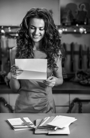 クリスマスの装飾されたキッチンで手紙を読んで幸せな若い主婦