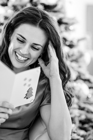 Smiling young woman reading christmas postcard