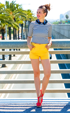 Full length portrait of happy elegant fashion-monger in yellow shorts and stripy shirt outdoors in the city looking into the distance Stock Photo