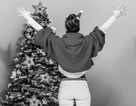 Seen from behind stylish woman in colorful clothes near Christmas tree isolated on yellow background rejoicing