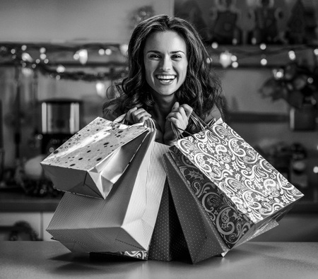 Smiling young woman with christmas shopping bags in christmas decorated kitchen