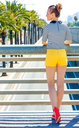 Seen from behind young fashion-monger in yellow shorts and stripy shirt in Barcelona, Spain looking into the distance
