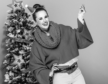 happy stylish woman in colorful clothes near Christmas tree on yellow background snapping with fingers