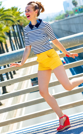 happy young fashion-monger in yellow shorts and stripy shirt against highway in the city having fun time