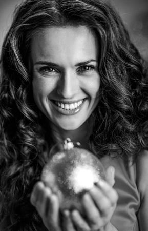 クリスマスボールを持つ笑顔の若い主婦の肖像 写真素材