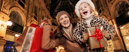 Portrait of happy young mother and daughter tourists in Galleria Vittorio Emanuele II in Milan, Italy with Christmas present box and shopping bags rejoicing