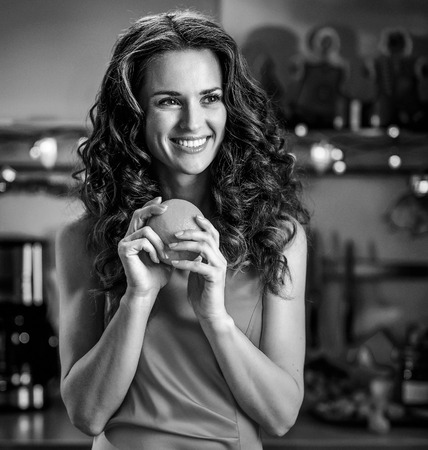 Happy young housewife with oranges in christmas decorated kitchen Фото со стока