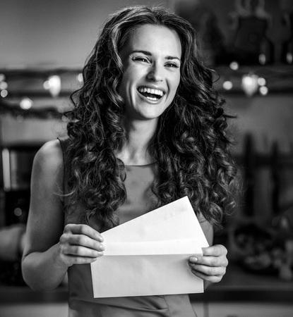 キッチンでクリスマスレターを持つ幸せな若い主婦の肖像画