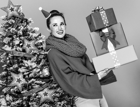 smiling modern woman in colorful clothes near Christmas tree on yellow background with pile of Christmas present boxes looking at copy space Фото со стока