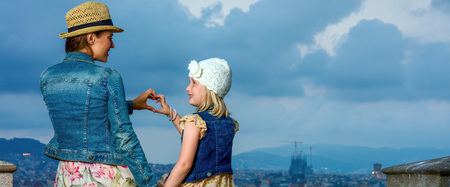 Perfect evening with stunning view. Seen from behind young mother and daughter tourists against city panorama of Barcelona, Spain showing heart shaped hands
