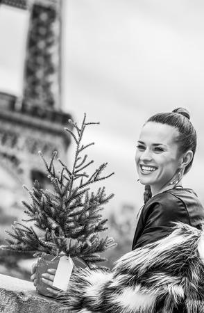 La saison des fêtes à Paris. Portrait de marchand de mode moderne heureux avec arbre de Noël en manteau de fourrure à Paris, France, regardant au loin Banque d'images - 94389367