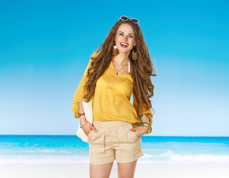 Perfect summer. Portrait of happy healthy woman in shorts and yellow blouse with white beach bag on the seashore