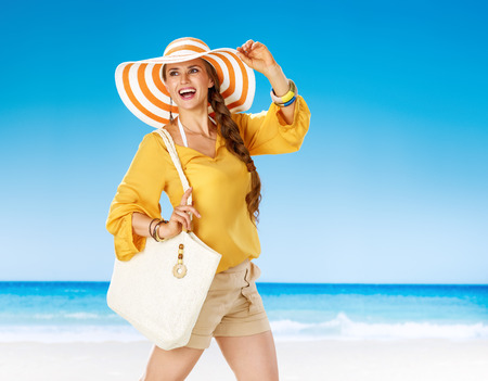 Perfect summer. smiling young woman in shorts and yellow blouse with white beach bag on the seashore looking into the distance
