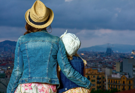 Perfect evening with stunning view. Seen from behind modern mother and child travellers against city panorama of Barcelona, Spain looking into the distance Stock Photo