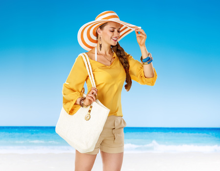 Perfect summer. Portrait of happy healthy woman in shorts and yellow blouse with white beach bag on the beach Stok Fotoğraf