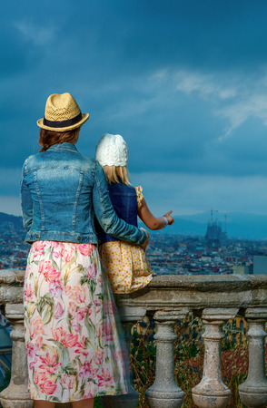 Perfect evening with stunning view. Seen from behind young mother and daughter tourists in Barcelona, Spain enjoying view