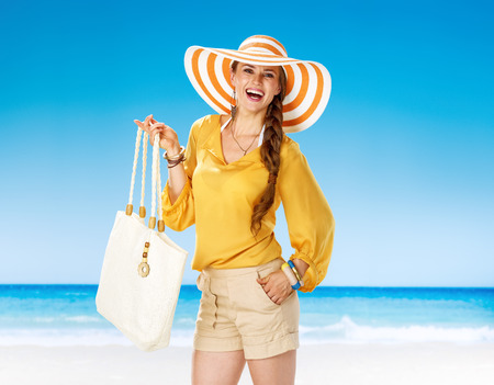 Perfect summer. Portrait of happy young woman in shorts and yellow blouse with white beach bag on the seacoast