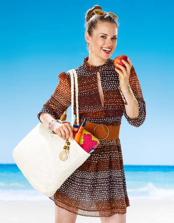 Perfect summer. happy young woman in summer dress with white beach bag on the beach eating an apple
