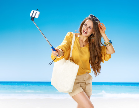 Perfect summer. happy woman in shorts and yellow blouse with white beach bag on the seashore taking selfie using selfie stick