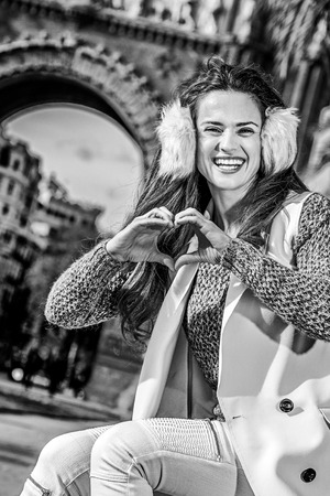 in Barcelona for a perfect winter. Portrait of happy modern fashion-monger in earmuffs in Barcelona, Spain showing heart shaped hands