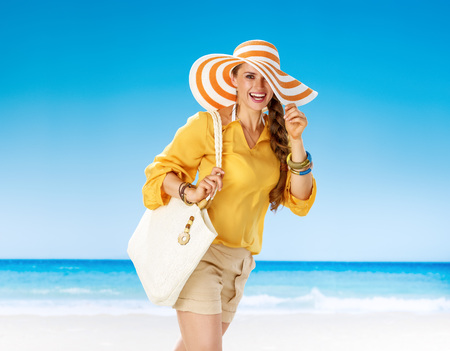 Perfect summer. Portrait of happy young woman in shorts and yellow blouse with white beach bag on the seashore