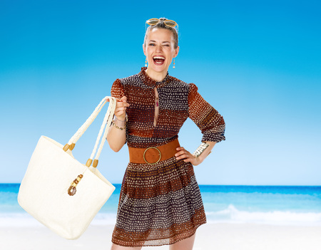 Perfect summer. smiling healthy woman in summer dress on the seacoast playing with white beach bag