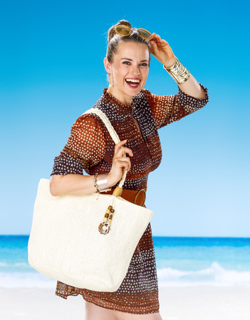 Perfect summer. Portrait of happy healthy woman in summer dress with white beach bag on the beach