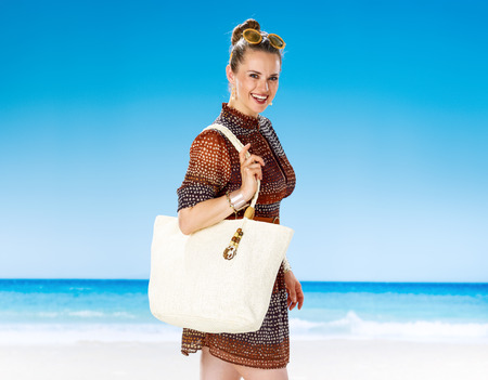 Perfect summer. Portrait of smiling young woman in summer dress with white beach bag on the seashore