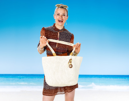 Perfect summer. smiling healthy woman in summer dress on the beach showing white beach bag